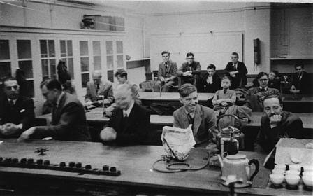 The picture shows members in the very early days of the Club, we are not certain but we believe this was taken at the Roxeth Manor School in the Science Laboratory.