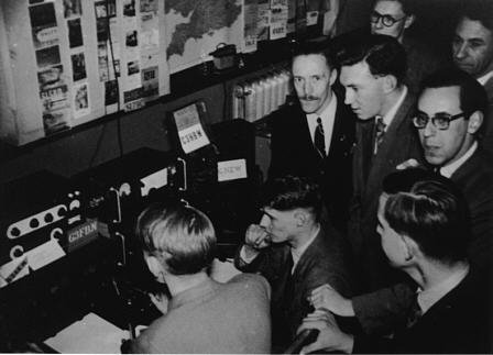 The picture shows enthusiastic Club members gathered around the radio at the Kodak exhibition. We recognise a couple of people in this picture: the chap with the moustache is Peter Parry, G3KOE; and the chap standing to Peter's front is Brian Hummerstone, G3HBR.